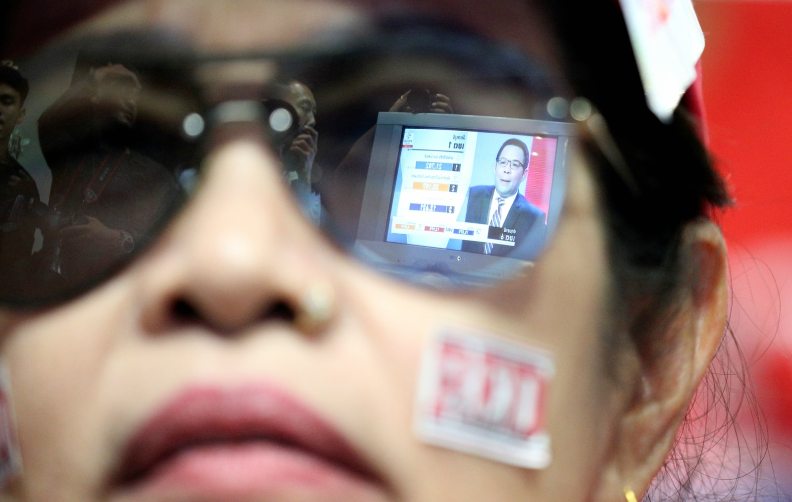 Live results are reflected in glasses of a supporter of Pheu Thai Party during the general election in Bangkok, Thailand, March 24, 2019. REUTERS/Athit Perawongmetha