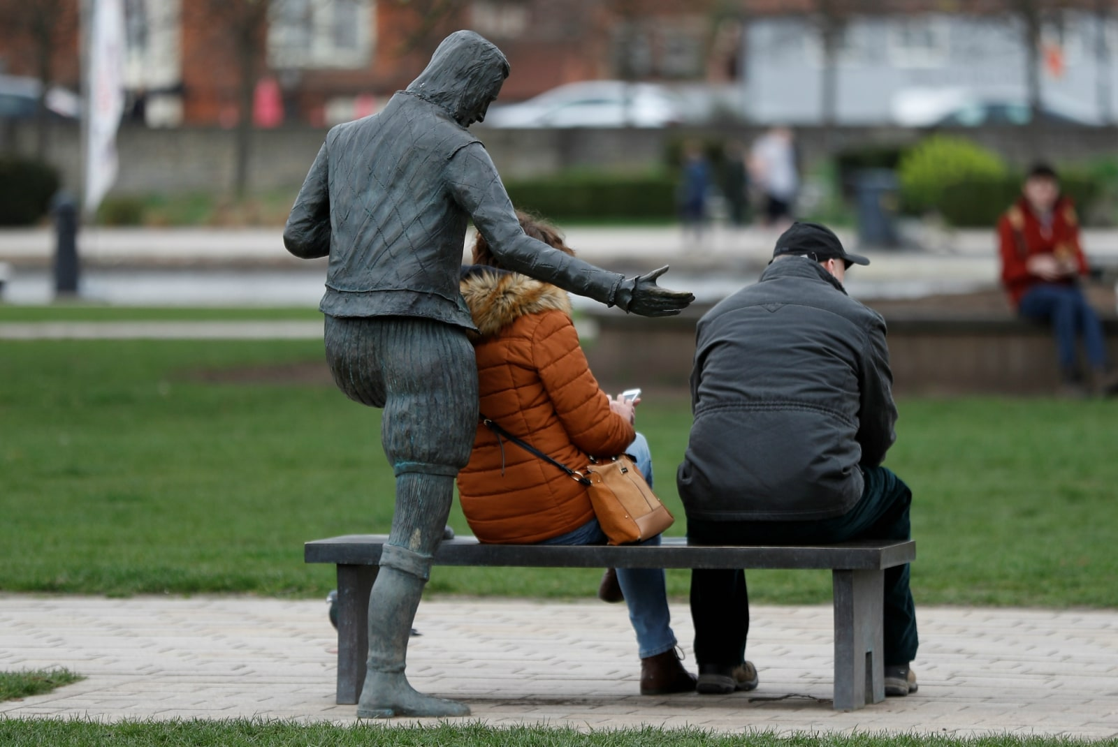 Visitors sit on a bench attached to a statue of writer William Shakespeare in the centre of Stratford-upon-Avon, Britain, March 22, 2019. REUTERS/Peter Nicholls/Files