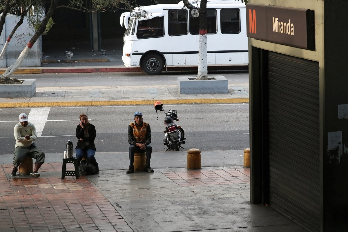 Locals sit outside a closed metro station during a blackout in Caracas. (REUTERS/Ivan Alvarado)