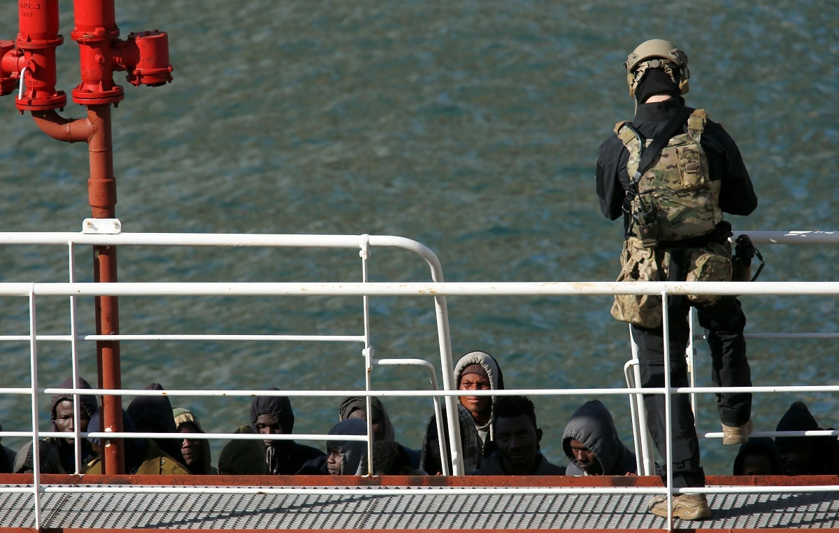A Maltese special forces soldier guards a group of migrants on the merchant ship. (REUTERS/Darrin Zammit Lupi)