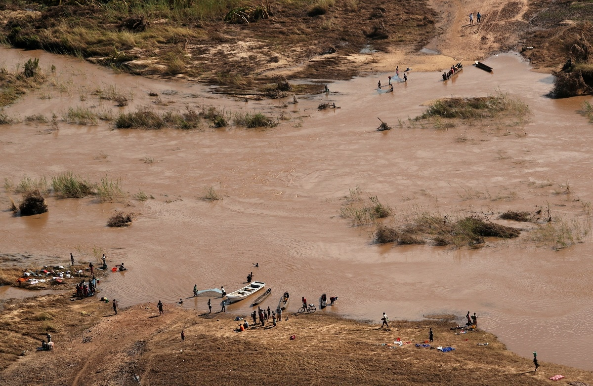 People stand on the banks where the bridge was washed away. (REUTERS/Mike Hutchings/File Photo)