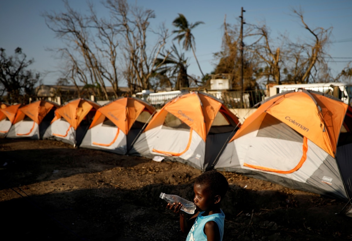A child walks past tents at a camp for people displaced in the aftermath of Cyclone Idai in Beira, Mozambique. (REUTERS/Mike Hutchings)