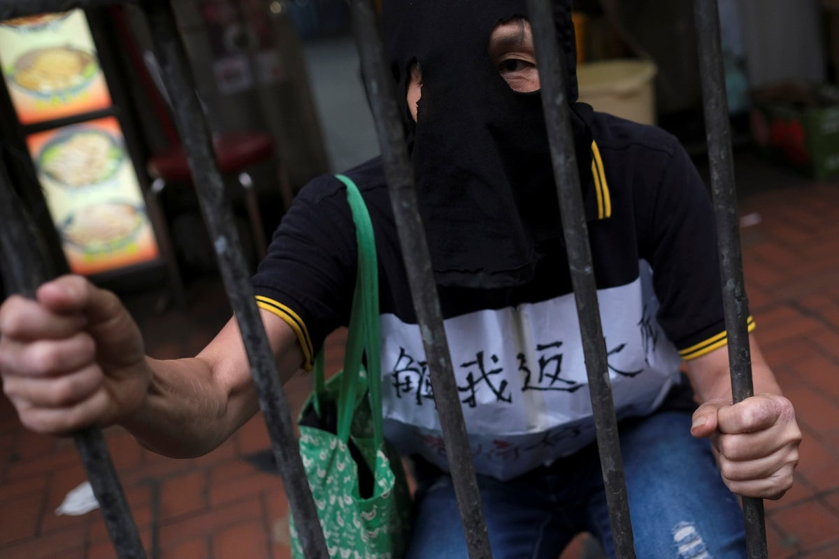 A masked demonstrator marches during the protest. (REUTERS/Tyrone Siu)