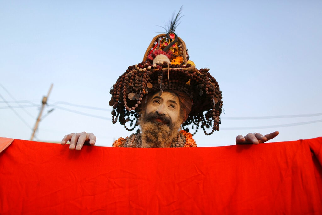 A Naga Sadhu or a naked Hindu holy man stands behind a piece of cloth hung to dry at Sangam, the confluence of the Rivers Ganges, Yamuna and mythical Saraswati during the Kumbh Mela or the Pitcher Festival, in Prayagraj, Uttar Pradesh state, India, Tuesday, February 19, 2019. (AP Photo/Rajesh Kumar Singh)