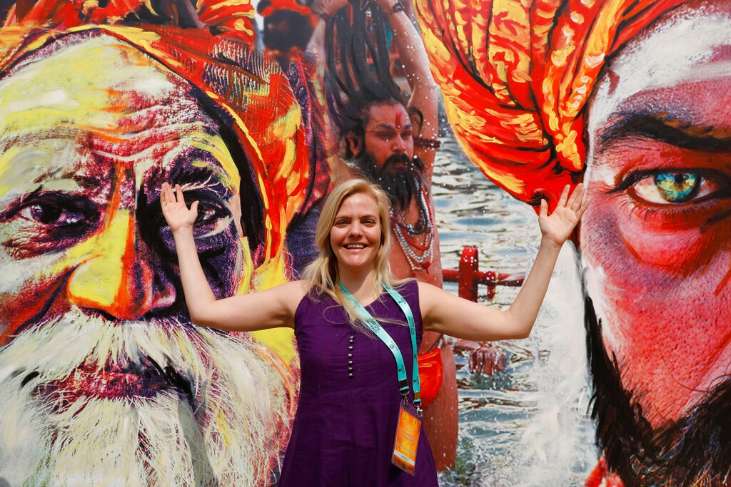 A foreign delegate stands for a photograph in front of giant posters of Sadhus at Sangam, the confluence of the Rivers Ganges, Yamuna and mythical Saraswati, during Kumbh festival in Prayagraj, India, Friday, February 22, 2019. More than 100 foreign delegates visited Kumbh on an invitation by the Indian Council for Cultural Relations (ICCR). (AP Photo/Rajesh Kumar Singh)