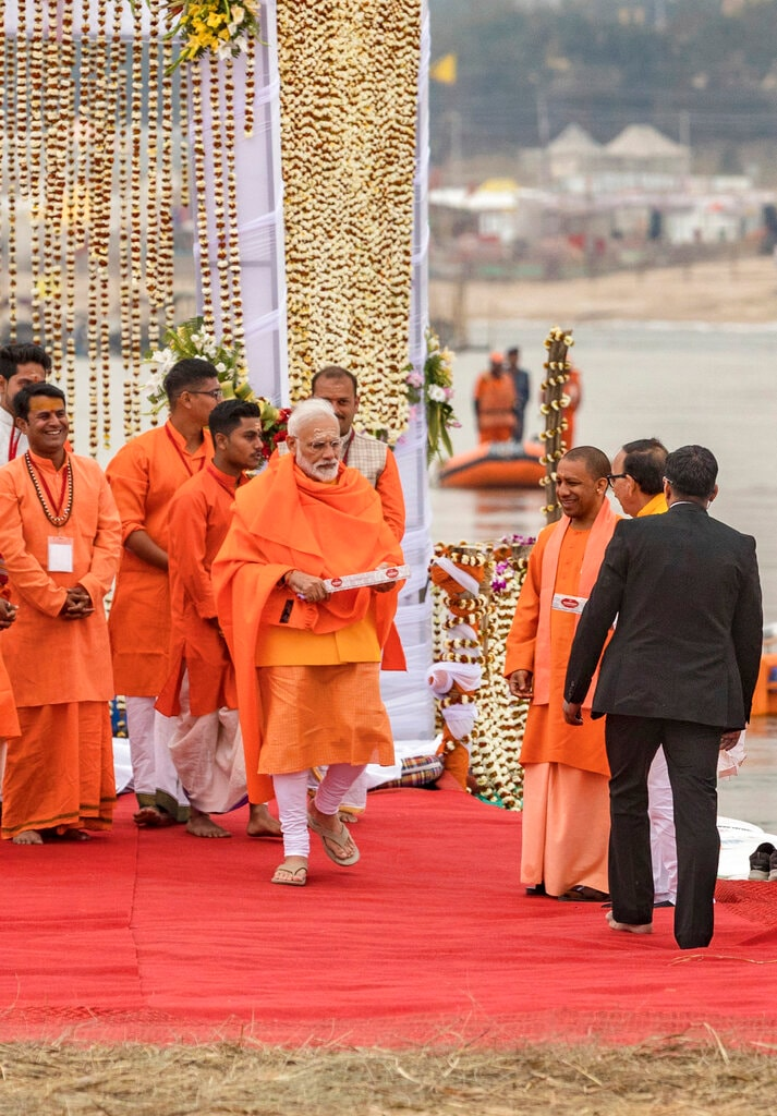 Prime Minister Narendra Modi, returns after taking a holy dip at Sangam, the confluence of the Rivers Ganges, Yamuna and mythical Saraswati, during Kumbh festival, in Allahabad, India, Sunday, February 24, 2019. Uttar Pradesh chief minister Yogi Adityanath is on second right. (AP Photo/ Rajesh Kumar Singh)