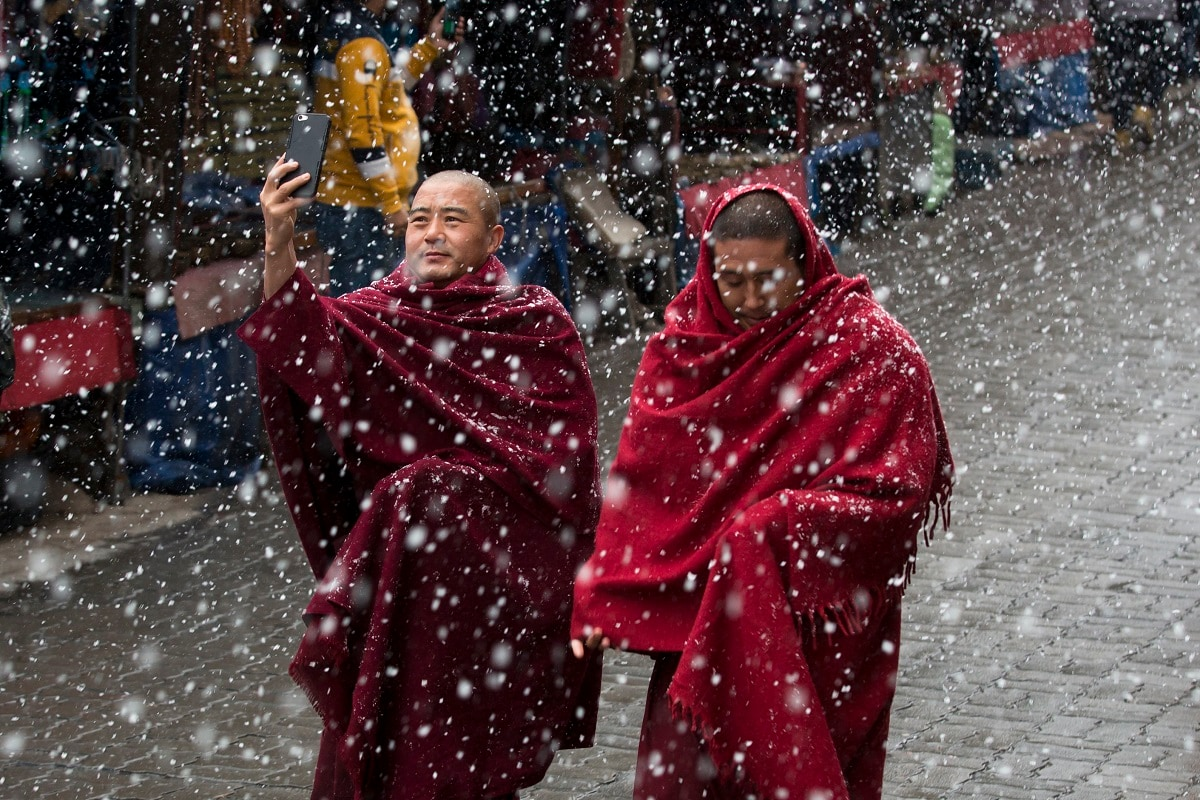 A Tibetan Buddhist monk uses his phone camera as he walks with another in the snow in Dharmsala. This Himalayan region saw another snowfall on Wednesday. (AP Photo/Ashwini Bhatia, File)