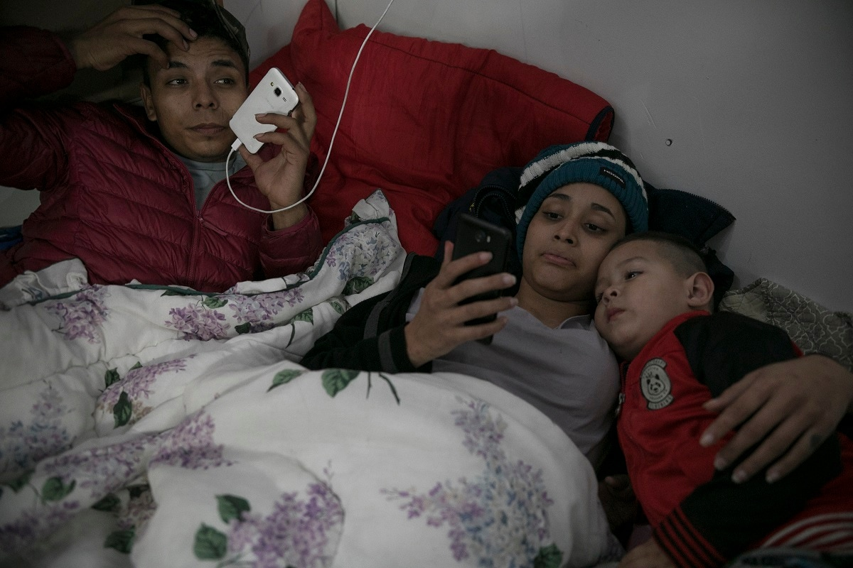 17-year-old Honduran migrant Josue Mejia Lucero, his girlfriend Milagro de Jesus Henriquez Ayala, 15, and Josue's 3-year-old nephew Jefferson, look at cell phones as they lie in bed at the Agape World Mission shelter in Tijuana, Mexico. Milagro and her sister Xiomara came in search of their father, who left them in Mexico's southern border city of Tapachula while he tried to get to the United States. (AP Photo/Emilio Espejel)