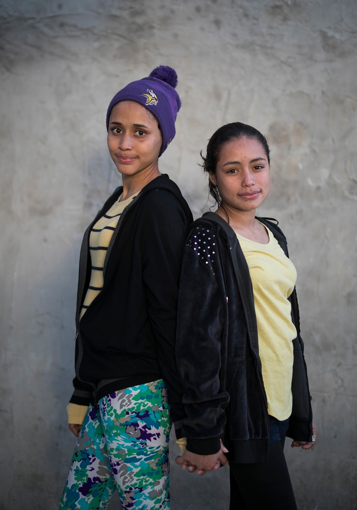 El Salvador migrant sisters 15-year-old Milagro de Jesus Henriquez Ayala, left, and Xiomara, 13, pose for a portrait at the Agape World Mission shelter in Tijuana, Mexico. The girls say they are too afraid to cross the border illegally after seeing the towering wall topped with concertina wire, especially since Milagro is nearly six months pregnant. (AP Photo/Emilio Espejel)
