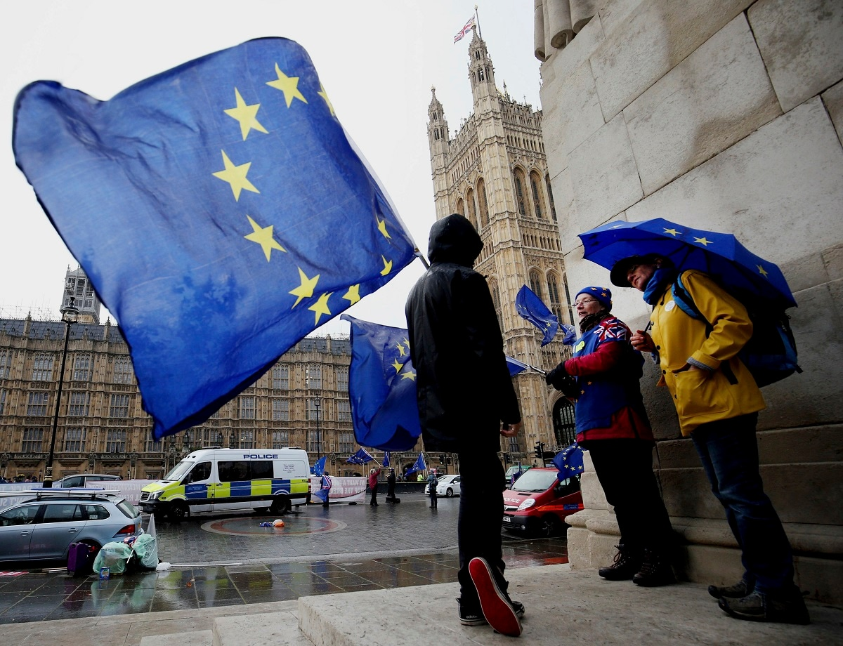 Remain supporters shelter from the wind and rain across the street from parliament in London. British Prime Minister Theresa May has offered Parliament the chance to delay Britain's scheduled March 29 departure if lawmakers fail to approve her divorce agreement with the bloc.(Jonathan Brady/PA via AP)