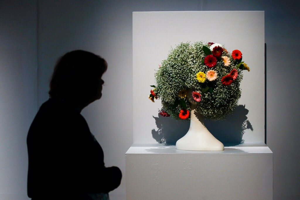 A visit views a backed pedestal arrangement by Karena Valentine and Eleanor P Deacon during a preview of the
