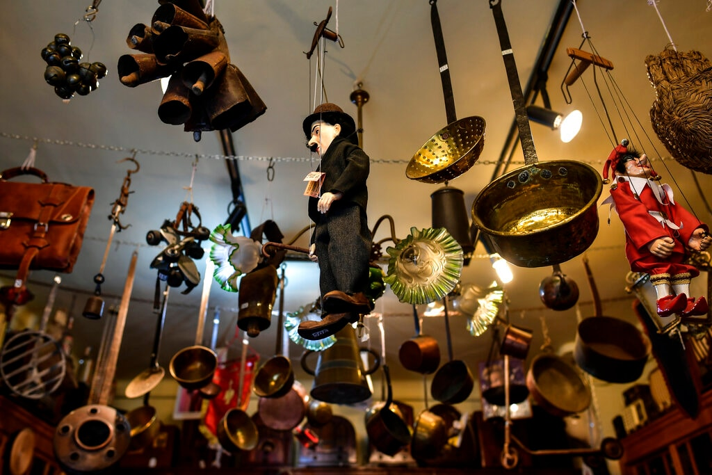 A lot of antiques are displayed in the shop belonging to Manuel Mosquera while people visit the antiques