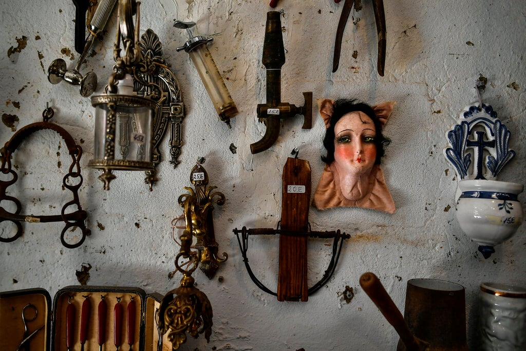 Some antiques offered in the shop of Manuel Mosquera are displayed while people visit the antiques market