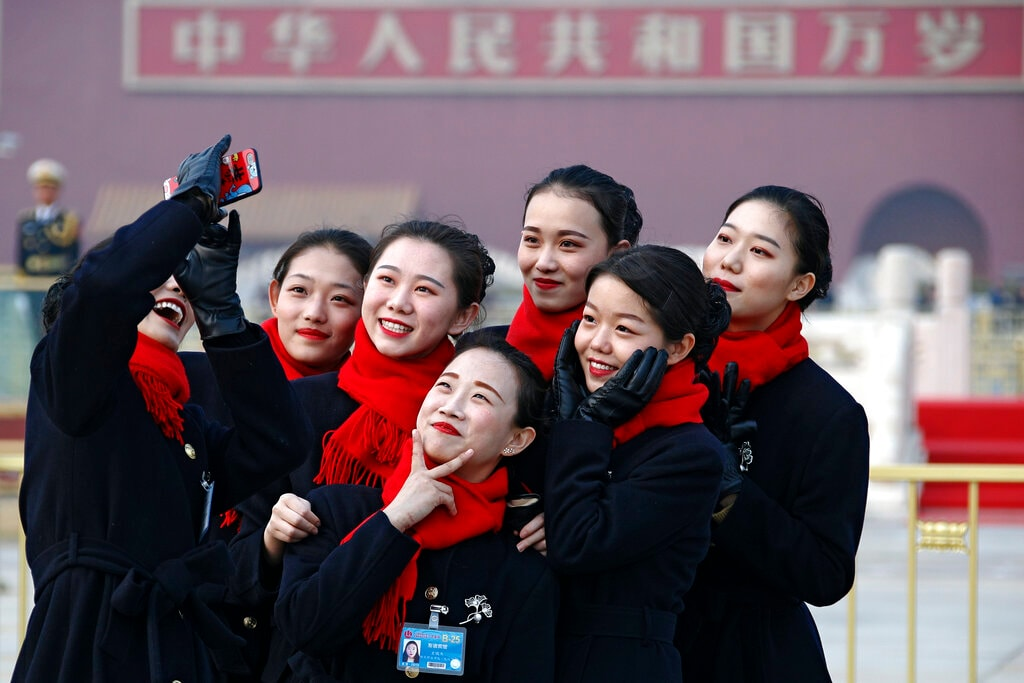 Hospitality staff take selfies on Tiananmen Square during the opening session of the Chinese People's Political Consultative Conference (CPPCC) held at the Great Hall of the People in Beijing, Sunday, March 3, 2019. (AP Photo/Andy Wong)