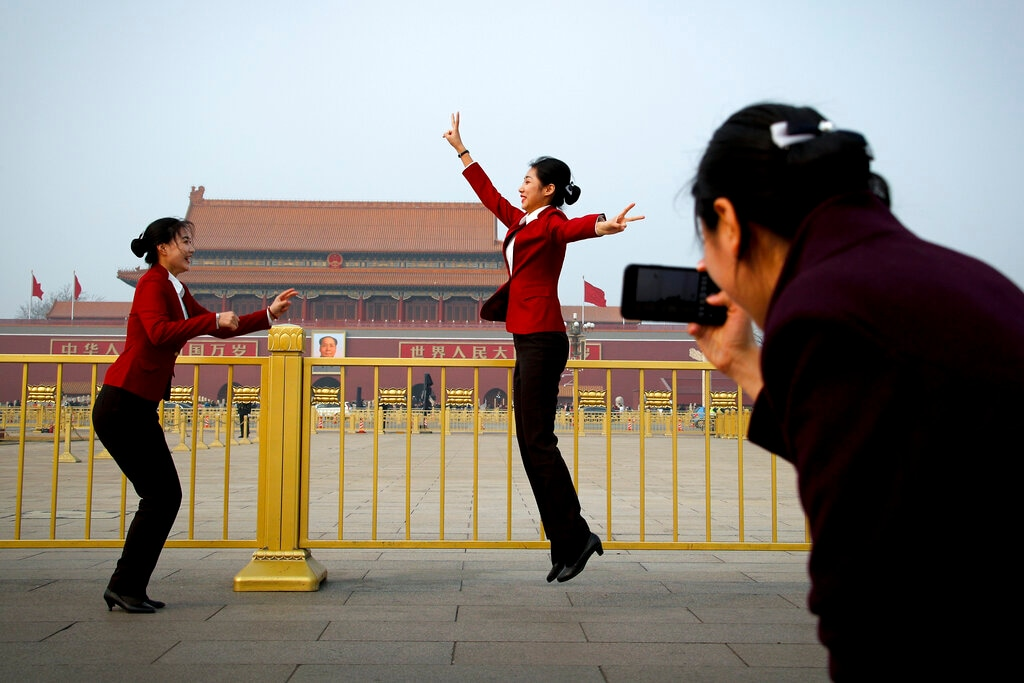Hospitality staff jump as they pose for their colleague on Tiananmen Square during the opening session of the Chinese People's Political Consultative Conference (CPPCC) held at the Great Hall of the People in Beijing, Sunday, March 3, 2019. (AP Photo/Andy Wong)