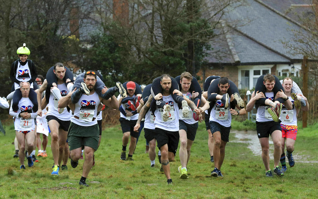 Competitors take part in the annual UK Wife Carrying Race at The Nower in Dorking, England, Sunday, March 3, 2019. In 2019, the UK Wife Carrying Race intends to send a squad of athletes to compete in the World Wife Carrying Championships in Finland in July 2019. (Gareth Fuller/PA via AP)