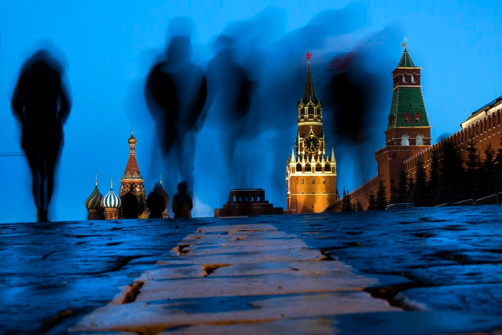 People walk through Red Square after sunset in Moscow, Russia, Sunday, March 3, 2019, with the St. Basil's left, and the Spasskaya Tower, second right, in the background. (AP Photo/Alexander Zemlianichenko)