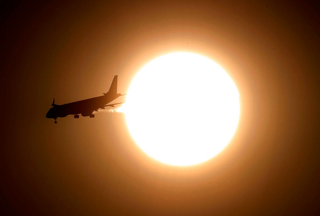 An airplane flies past the sun in Mexico City, early Sunday, March 3, 2019. (AP Photo/Marco Ugarte)