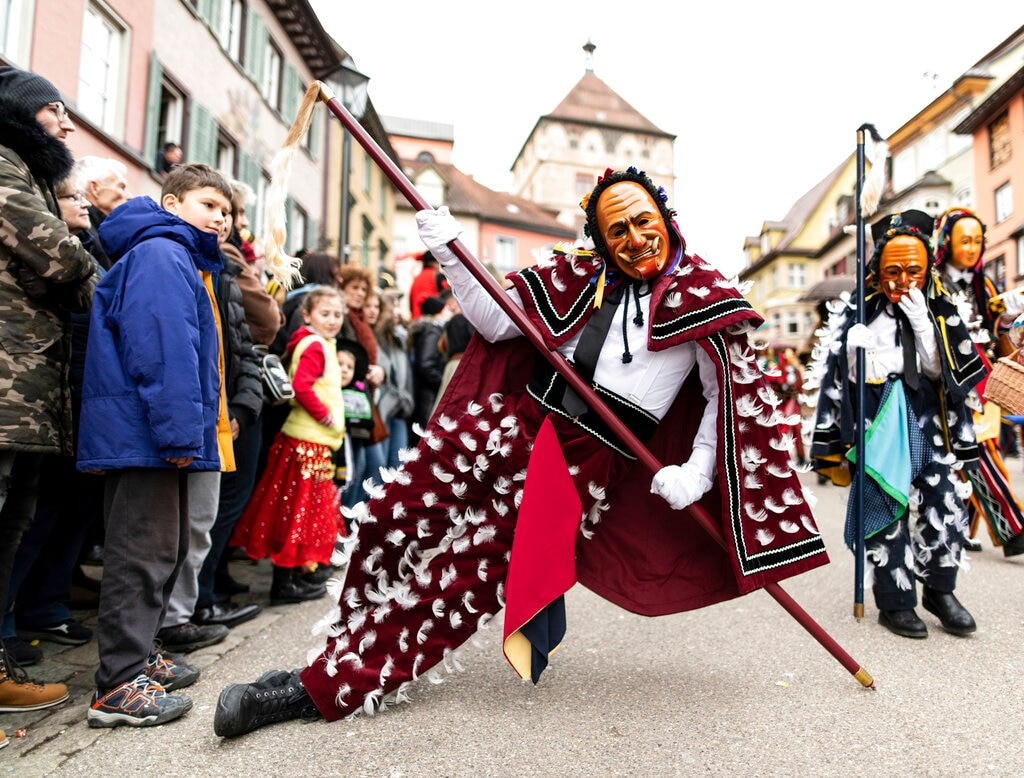 A Federahannes, a Rottweiler fool figure, leans on his stick while jumping during the traditional 'Rottweiler Narrensprung', (Rottweil Fools Jump), carnival celebrations in Rottweil, Germany, Monday, March 4, 2019. (Patrick Seeger/dpa via AP)