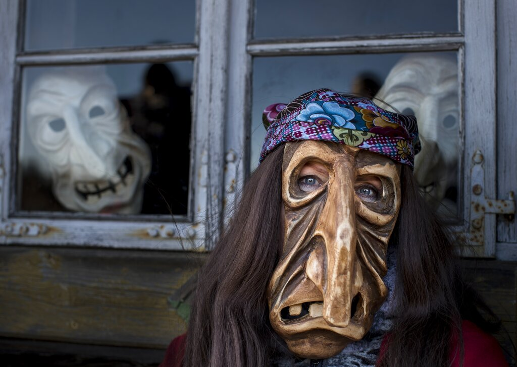 In this photo taken on Saturday, March 2, 2019, a performer wearing a traditional carnival mask takes part in Shrovetide celebrations, in Rumsiskes village, some 89 kilometers (56 miles) north of Vilnius, Lithuania. A strange scenario took place in this central Lithuania village this weekend as chanting devils, goats, witches and others filled the streets to chase winter away. (AP Photo/Mindaugas Kulbis)