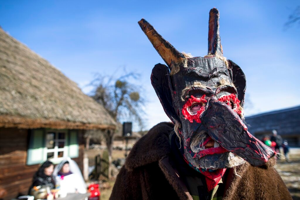 In this photo taken on Saturday, March 2, 2019, a performer wearing a traditional carnival mask takes part in Shrovetide celebrations, in Rumsiskes village, some 89 kilometers (56 miles) north of Vilnius, Lithuania. (AP Photo/Mindaugas Kulbis)