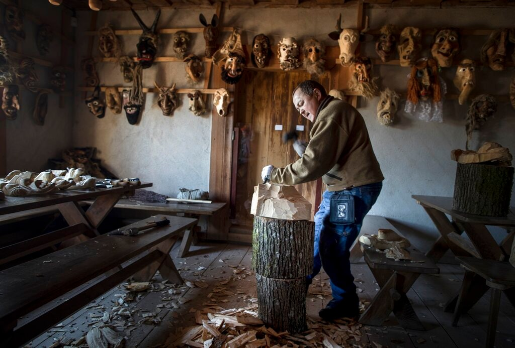 In this photo taken on Saturday, March 2, 2019, woodcarver Saulius Tamulis works on a new mask during Shrovetide celebrations, in Rumsiskes village, some 89 kilometers (56 miles) north of Vilnius, Lithuania. (AP Photo/Mindaugas Kulbis)