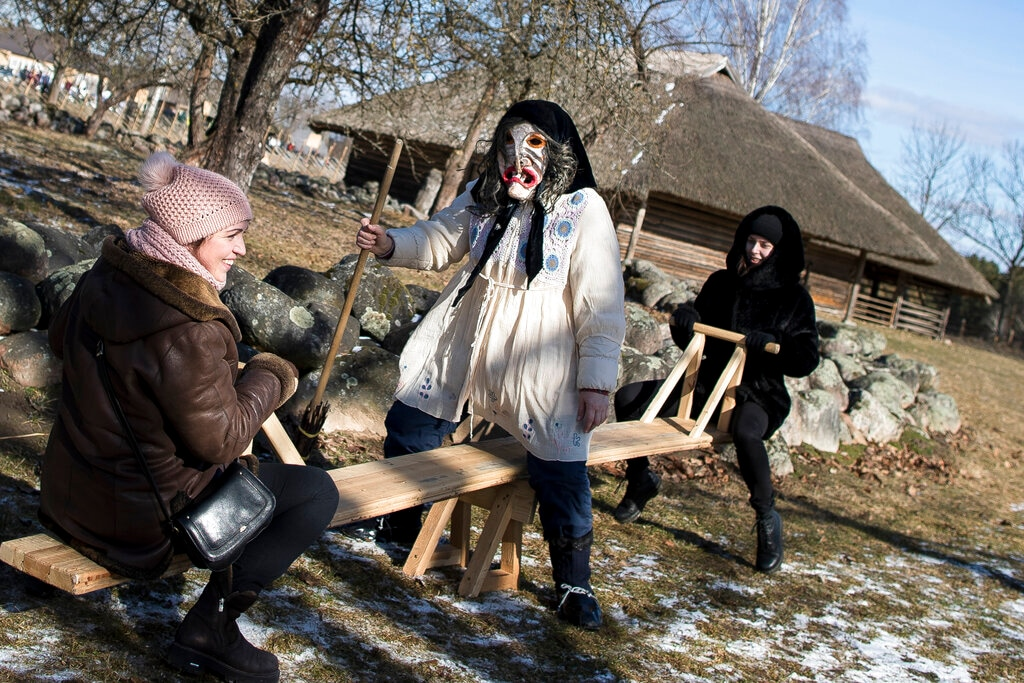 In this photo taken on Saturday, March 2, 2019, A performer wearing a traditional carnival mask, center, flirts with the participants of Shrovetide celebrations, in Rumsiskes village, some 89 kilometers (56 miles) north of Vilnius, Lithuania. (AP Photo/Mindaugas Kulbis)