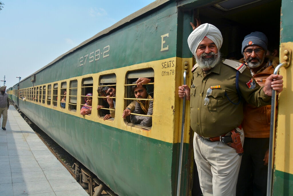 An Indian policeman and passengers from Pakistan look on from the Samjhauta Express train as it arrives in Atari, India, Monday, March 4, 2019. A Pakistani railway official said the key train service with neighboring India has resumed in another sign of easing tensions between the two nuclear-armed rivals since a major escalation last week over Kashmir region. (AP Photo/Prabhjot Gill)