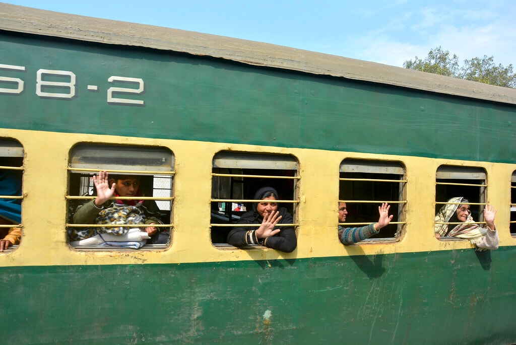 Passengers from Pakistan wave to media from the Samjhauta Express train as it arrives in Atari, India, Monday, March 4, 2019. A Pakistani railway official said the key train service with neighboring India has resumed in another sign of easing tensions between the two nuclear-armed rivals since a major escalation last week over Kashmir region. (AP Photo/Prabhjot Gill)