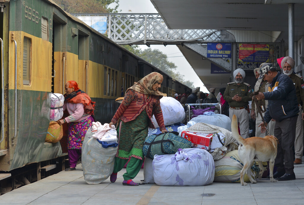 Passengers from Pakistan unload their belongings from the Samjhauta Express train as it arrives in Atari, India, Monday, March 4, 2019. A Pakistani railway official said the key train service with neighboring India has resumed in another sign of easing tensions between the two nuclear-armed rivals since a major escalation last week over Kashmir region. (AP Photo/Prabhjot Gill)