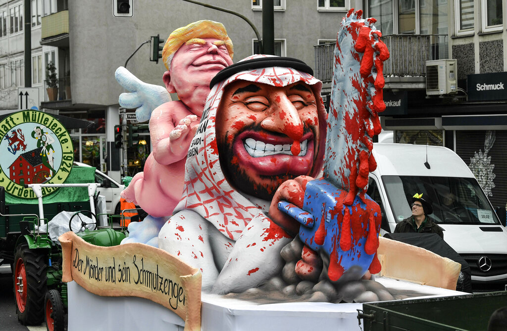 A carnival float depicts President Donald Trump as an angel of peace behind Saudi Crown Prince Mohammed bin Salman with a bloody chain saw prior to the traditional carnival parade in Duesseldorf, Germany, on Monday, March 4, 2019. (AP Photo/Martin Meissner)