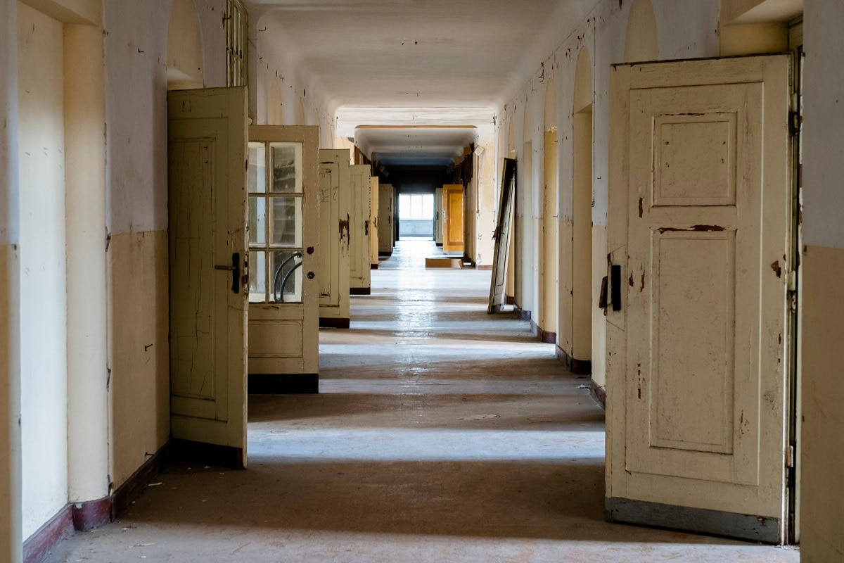 The doors stand open in a corridor of the abandoned