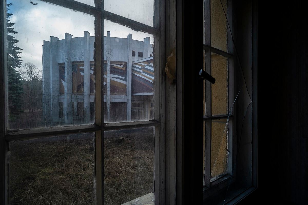 This photo shows view out of a window in the abandoned