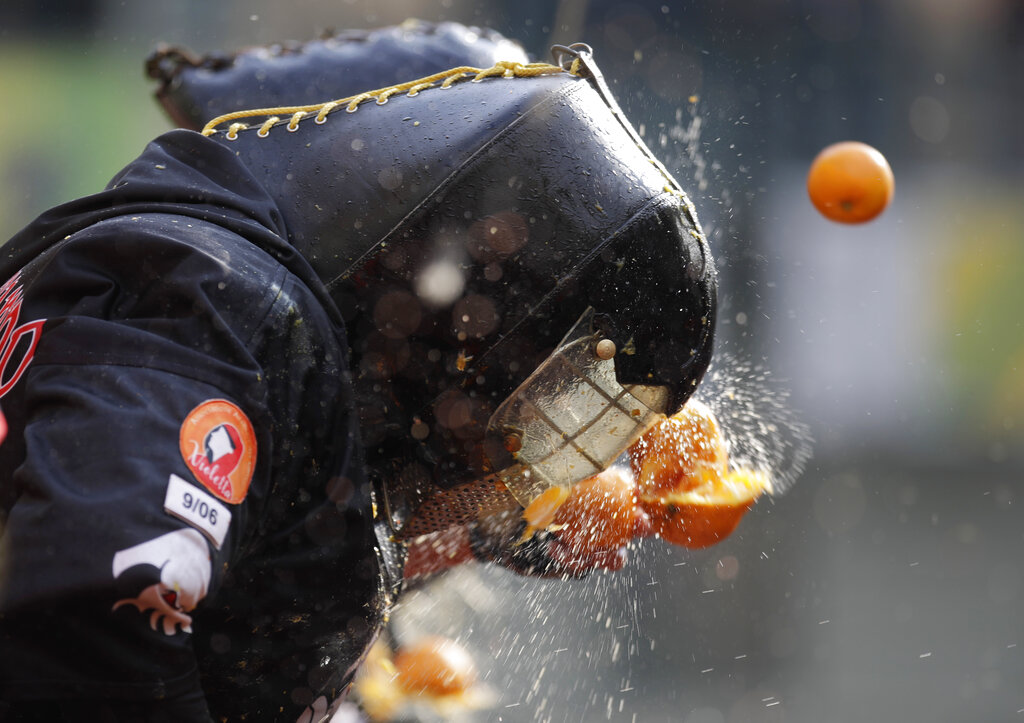 An orange hits a person wearing a protective helmet and costumes as part of Carnival celebrations in the northern Italian Piedmont town of Ivrea, Monday, March 4, 2019.  (AP Photo/Luca Bruno)