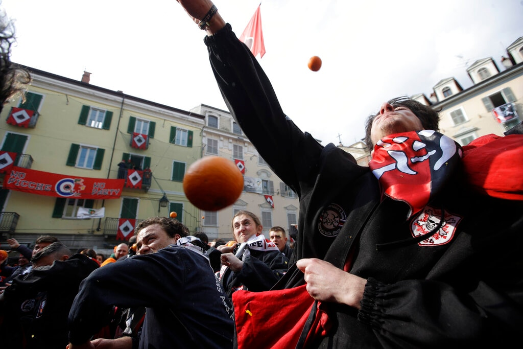 People wearing protective helmets and costumes throw oranges as part of Carnival celebrations in the northern Italian Piedmont town of Ivrea, Monday, March 4, 2019. (AP Photo/Luca Bruno)