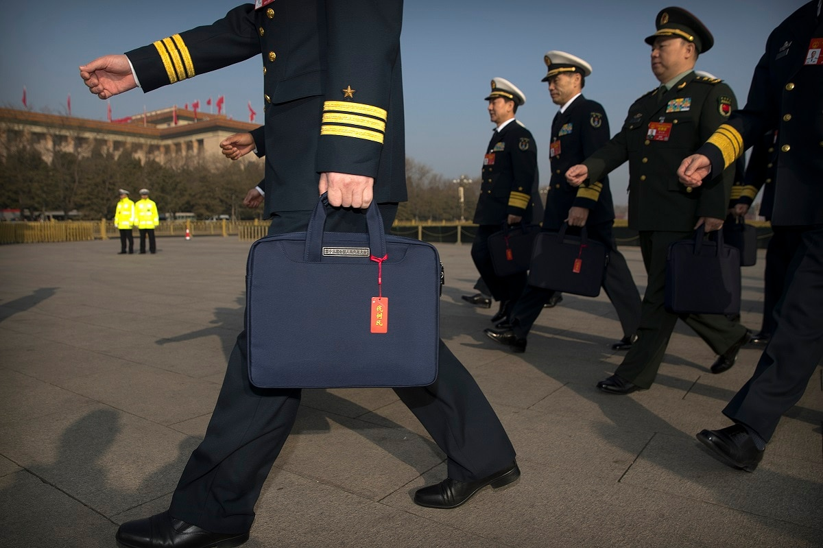 Military delegates carry satchels with individual nametags as they arrive for a meeting on the eve of the opening session of China's National People's Congress (NPC) at the Great Hall of the People in Beijing. (AP Photo/Mark Schiefelbein)