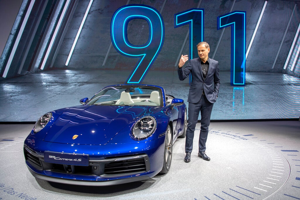 Oliver Blume, CEO of the car manufacturer Porsche, presents the new 'Porsche 911 Carrera 4S' cabriolet during the press day at the 89th Geneva International Motor Show in Geneva, Switzerland, Tuesday, March 05, 2019. The 'Geneva International Motor Show' takes place in Switzerland from March 7 until March 17, 2019. Automakers are rolling out new electric and hybrid models at the show as they get ready to meet tougher emissions requirements in Europe - while not forgetting the profitable and popular SUVs and SUV-like crossovers. (Martial Trezzini/Keystone via AP)