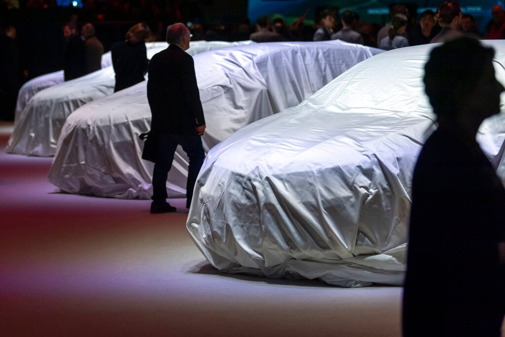 Visitors look at veiled Renalut cars during the press day at the '89th Geneva International Motor Show' in Geneva, Switzerland, Tuesday, March 05, 2019. The 'Geneva International Motor Show' takes place in Switzerland from March 7 until March 17, 2019. Automakers are rolling out new electric and hybrid models at the show as they get ready to meet tougher emissions requirements in Europe - while not forgetting the profitable and popular SUVs and SUV-like crossovers. (Martial Trezzini/Keystone via AP)