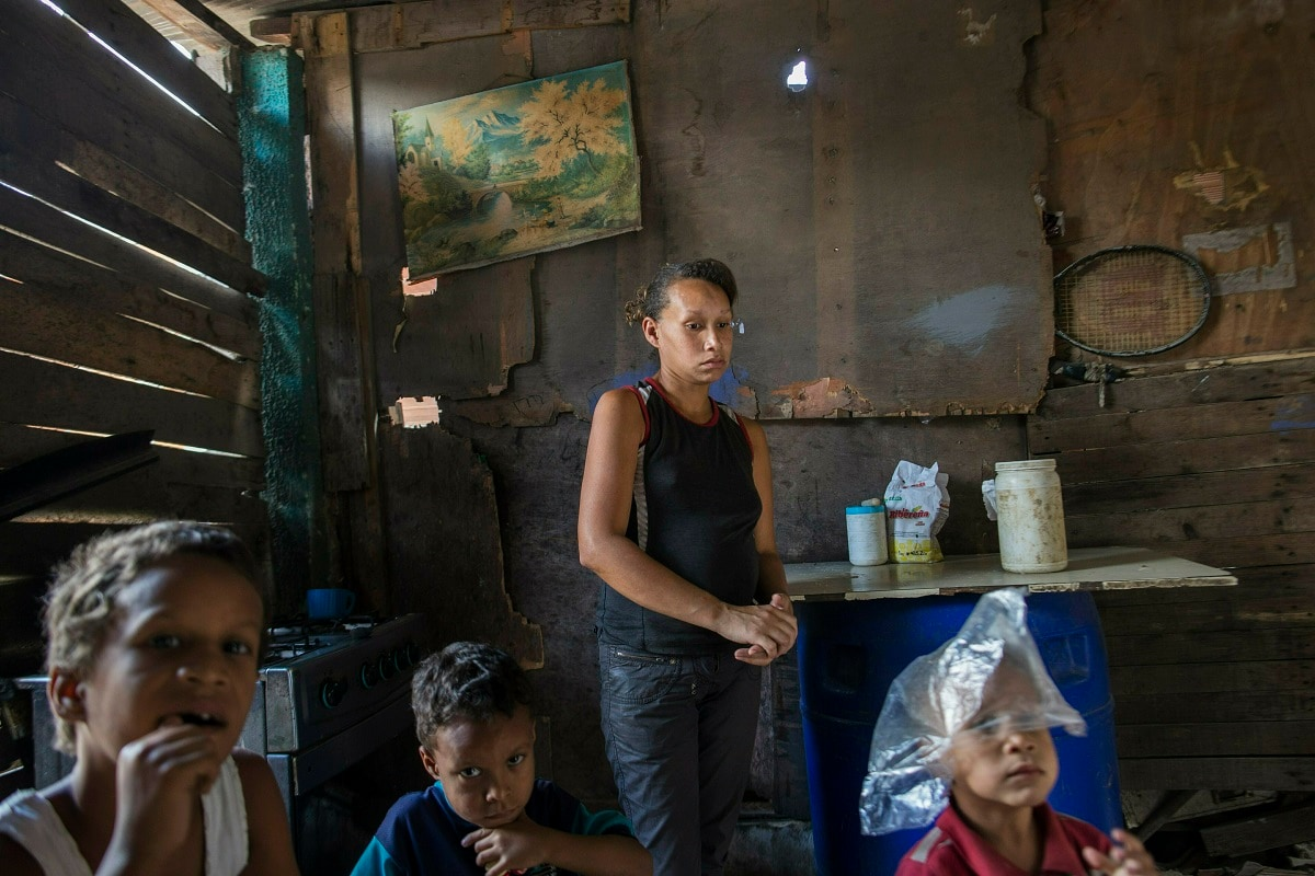 Francis Ojeda stands in her living room with her sons Moises, 8, from left, Joyker, 5, and Eduardo, 4, in the Petare slum, in Caracas, Venezuela. The scarcity of milk and other basic products has been turning the poor against socialist President Nicolas Maduro. Most Venezuelans blame him for the economic crisis. (AP Photo/Rodrigo Abd)
