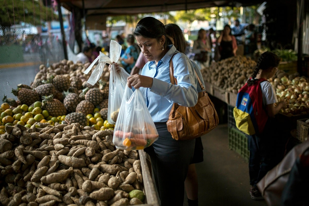 Carmen Victoria Gimenez, 43, shops at a farmers market in the middle-class district of Los Dos Caminos, in Caracas, Venezuela.