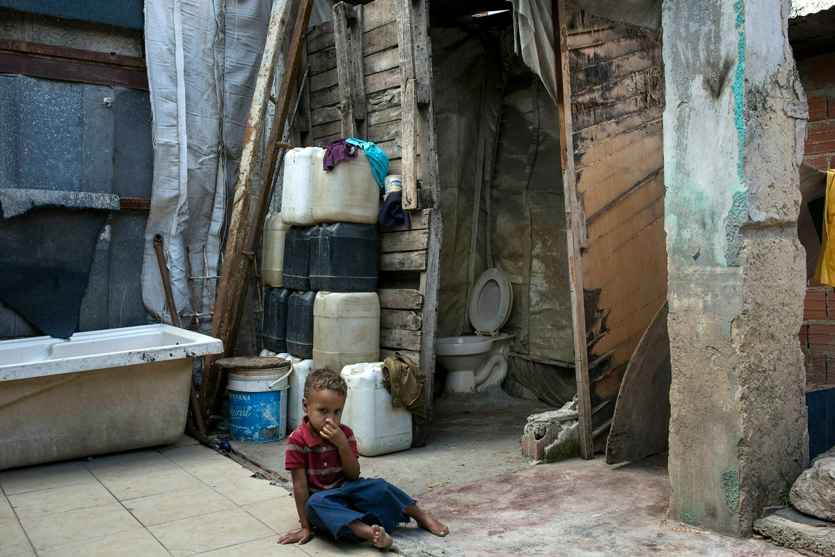 Eduardo Ojeda, 4, sits in an open space of his home in the Petare slum, in Caracas, Venezuela. Notoriously poor and crime-ridden, the shanty town's residents struggle daily with scarce running water and frequent blackouts. (AP Photo/Rodrigo Abd)