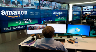 FILE- In this Sept. 4, 2018, file photo a Nasdaq employee monitors market activity in New York, with Amazon's logo on display in the background. The bull market in stocks started with the U.S. still reeling from the Great Recession in March 2009. The bull turns 10 this weekend, having survived threats such as a debt crisis in Europe (2011), a slowdown in the Chinese economy (2015-2016), and fears of inflation and rising interest rates in the U.S. (AP Photo/Mark Lennihan, File)