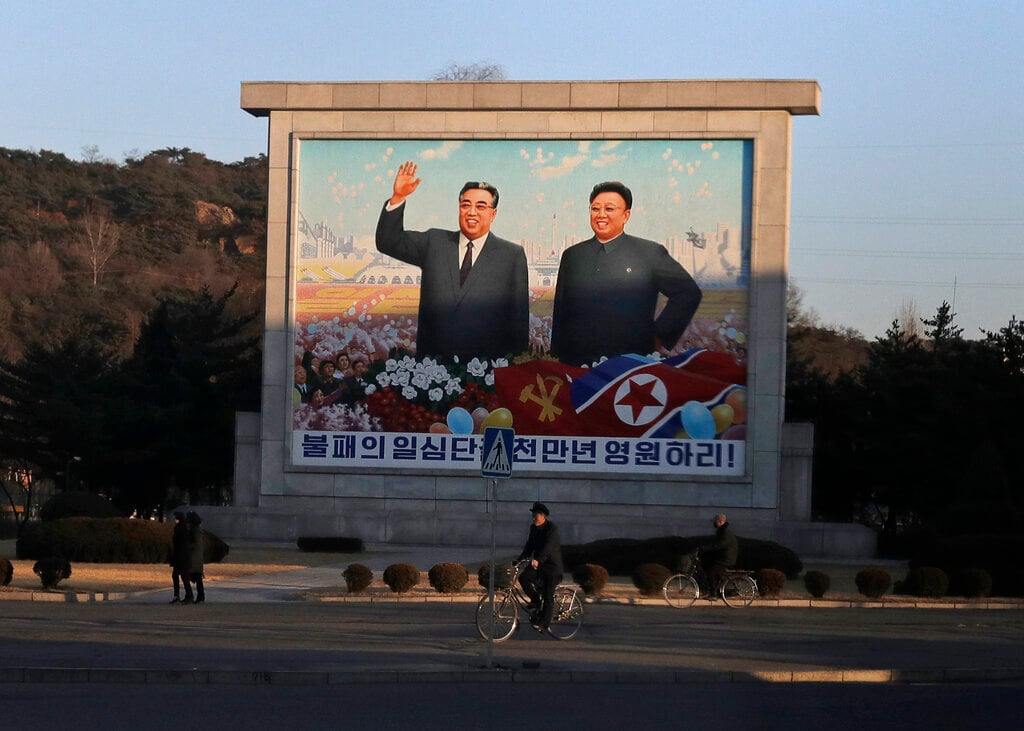 Men ride their bicycle past a mural of late North Korean leaders Kim Il Sung, left, and his son Kim Jong Il in Pyongyang, North Korea, Thursday, March 7, 2019. (AP Photo/Dita Alangkara)
