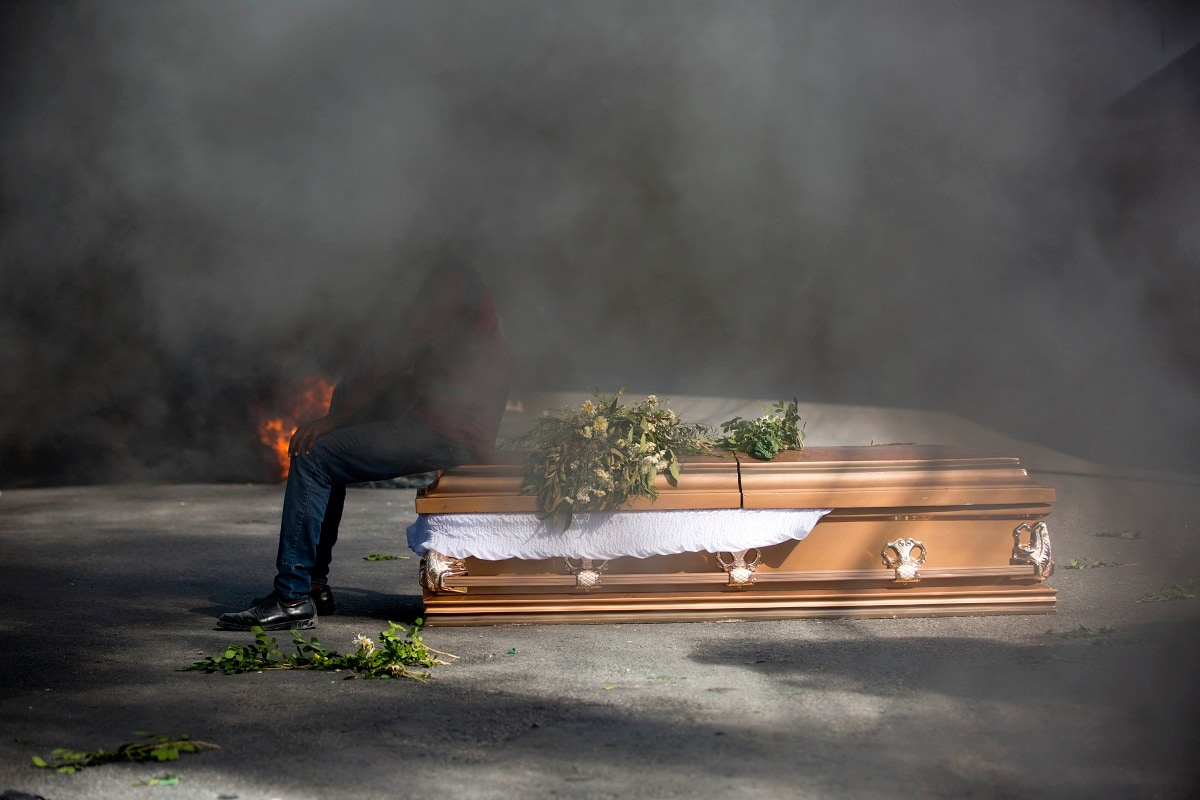 A demonstrator sits on the coffin containing the body of a protester who was killed during previous protests in Port-au-Prince, Haiti. Protesters are angry about skyrocketing inflation and the government's failure to prosecute embezzlement from a multi-billion Venezuelan program that sent discounted oil to Haiti. (AP Photo/Dieu Nalio Chery)