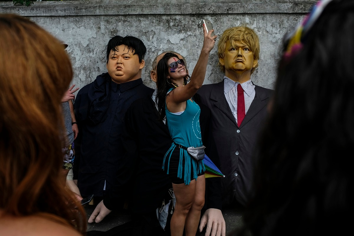 A woman takes a selfie next to giant dolls depicting US President Donald Trump, right, and North Korean leader Kim Jong-un, during carnival celebrations in Olinda, Pernambuco state, Brazil. (AP Photo/Diego Herculano)