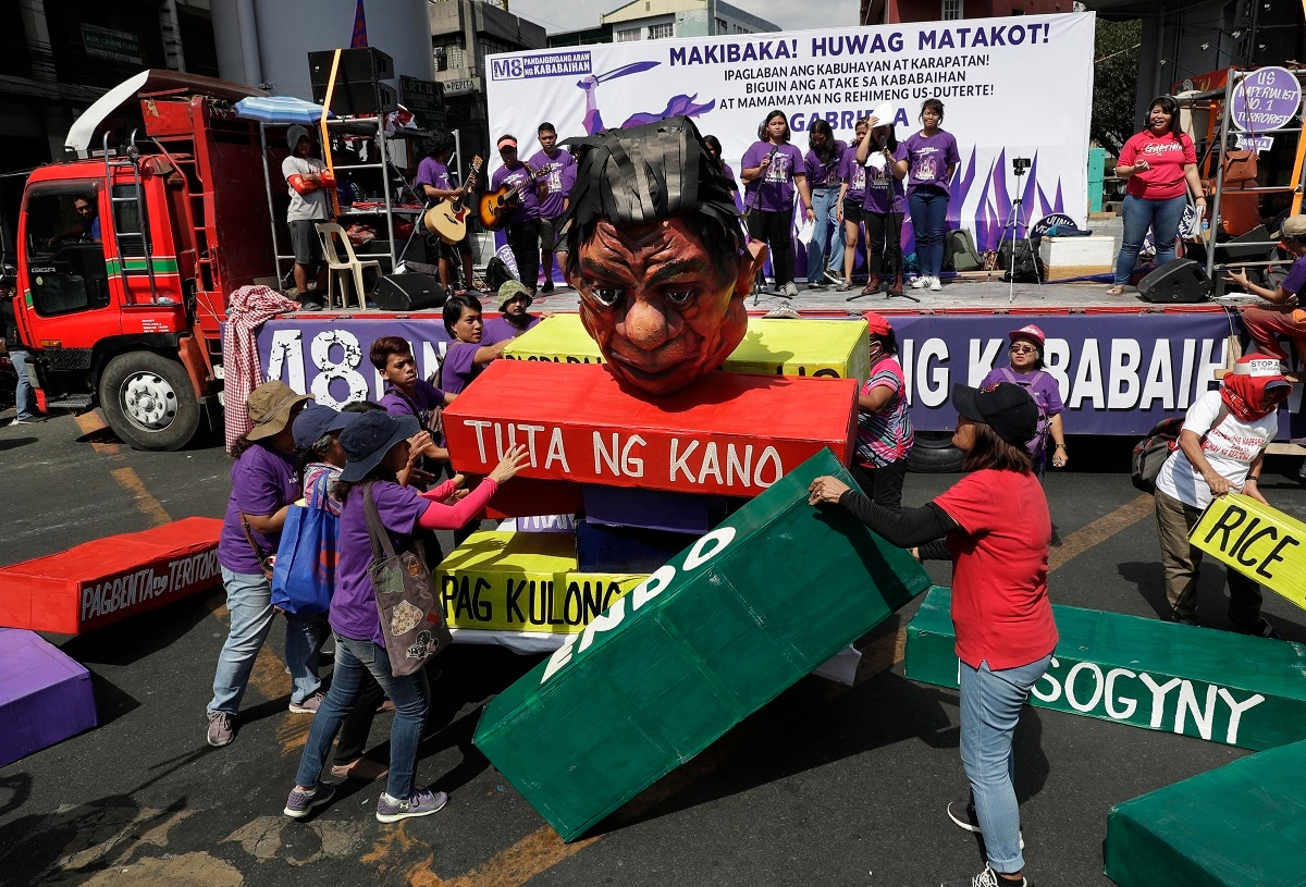 Women activists topple an effigy of Philippine President Rodrigo Duterte as they mark International Women's Day during a rally near the Malacanang presidential palace in Manila, Philippines. The group criticized Duterte, opposed martial law in Mindanao and called for equal rights. (AP Photo/Aaron Favila)