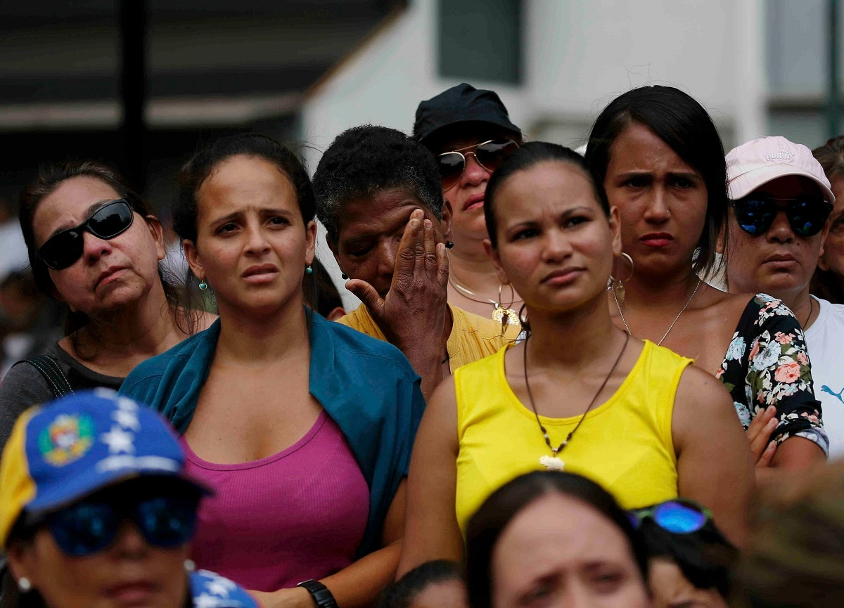 A woman wipes away tears as she stands with others listening to Venezuelan opposition leader Juan Guaido. (AP Photo/Eduardo Verdugo)