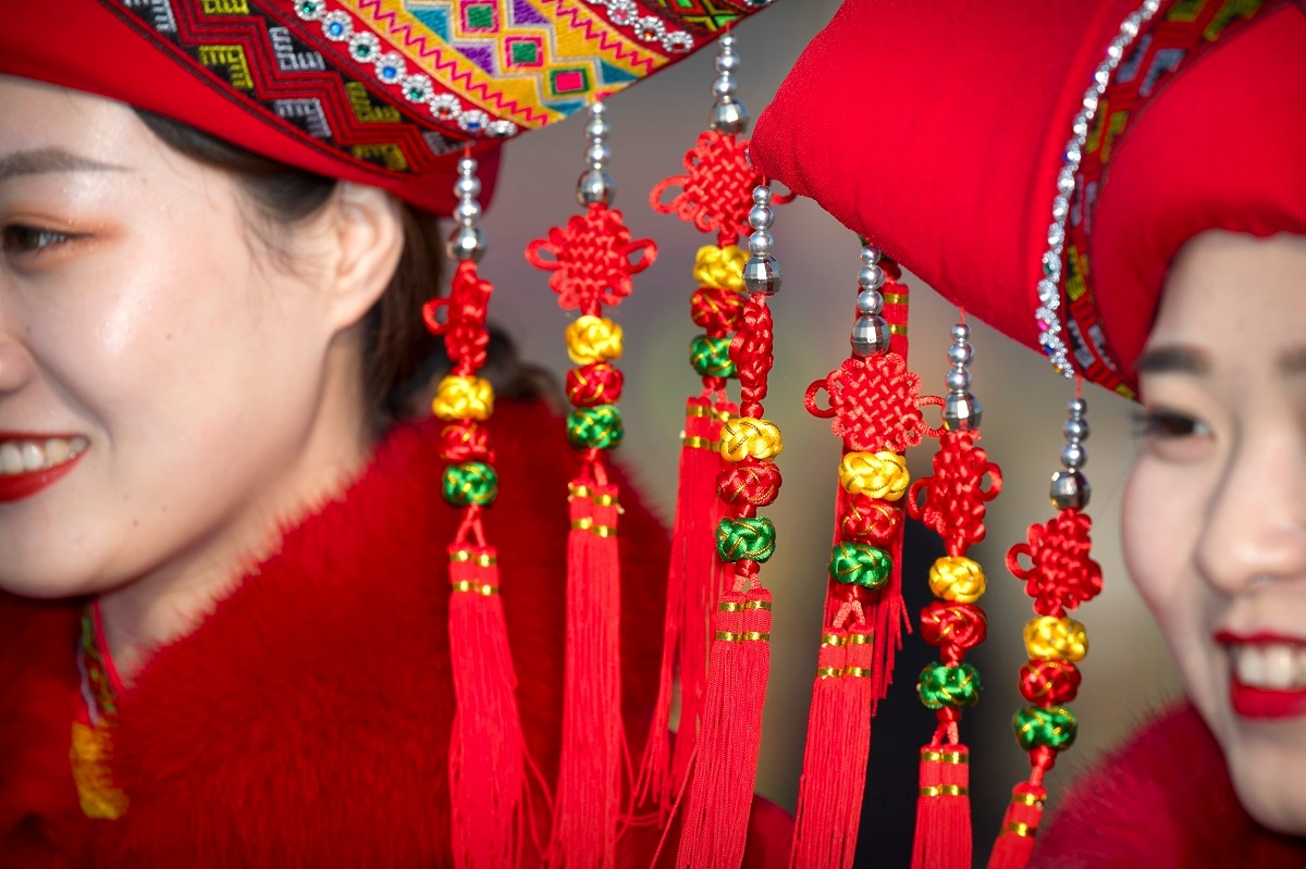 Decorations dangle from the hats of bus ushers in ethnic minority dress as they pose for a group photo during the opening session of China's National People's Congress (NPC) at the Great Hall of the People in Beijing. (AP Photo/Mark Schiefelbein)