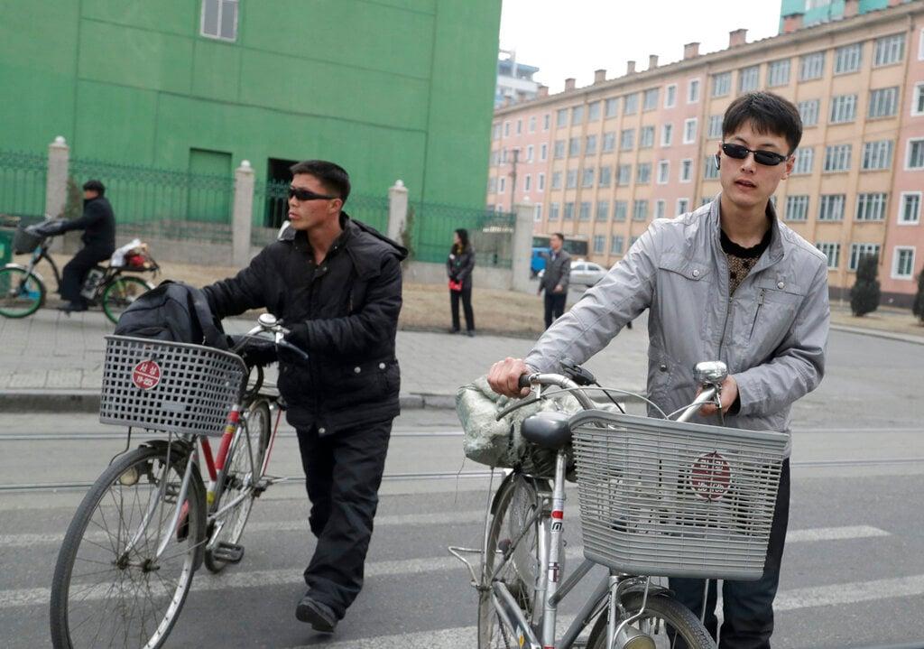North Korean men push their bicycles as they cross a road in Pyongyang, North Korea, Saturday, March 9, 2019. (AP Photo/Dita Alangkara)