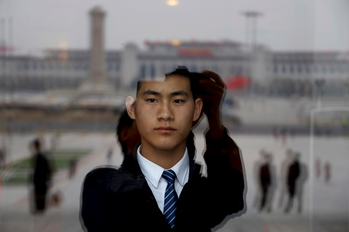A security officer stands on duty behind a glass window reflecting Tiananmen Square at the Great Hall of the People where a session of the Chinese People's Political Consultative Conference is held in Beijing. (AP Photo/Ng Han Guan)